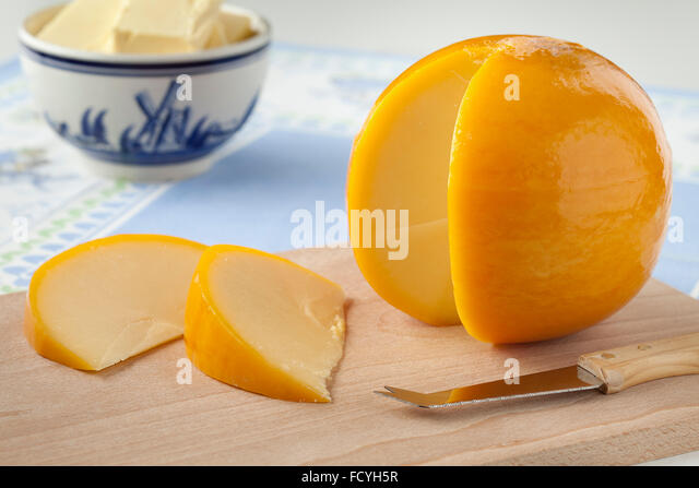 Yellow round Edam cheese with slices on a cutting board - Stock Image