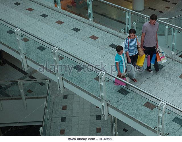 Family carrying shopping bags in mall - Stock-Bilder