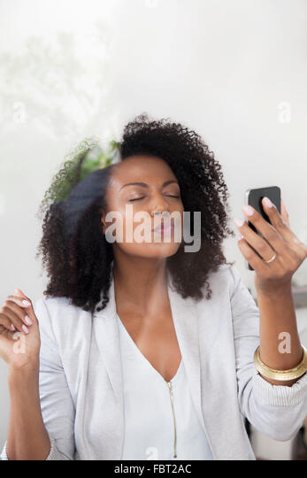 Woman blowing kiss at smartphone while doing video chat - Stock-Bilder