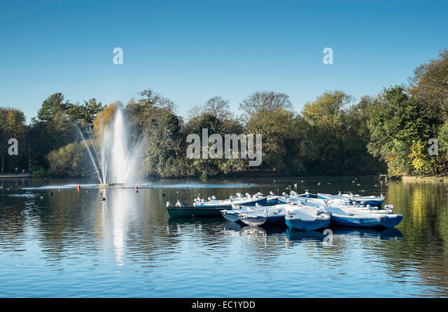 pretty scenic boating lake pond park boats London - Stock Image
