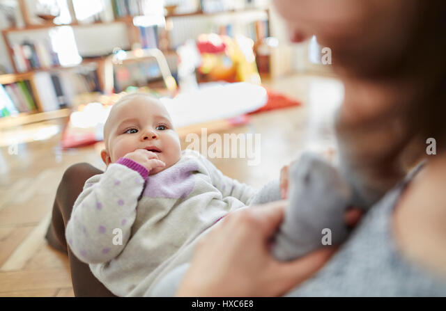 Mother holding baby daughter in lap - Stock Image