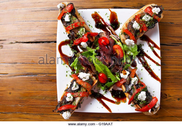 Portobello mushroom bites with roasted red peppers and goat cheese - Stock Image