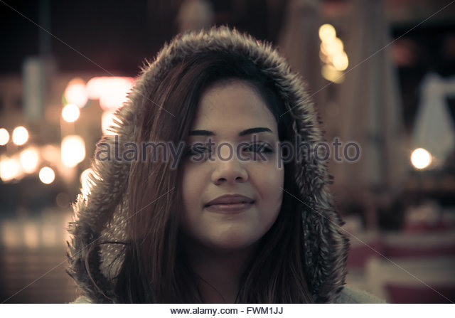 Close-Up Portrait Of Smiling Young Woman At Night - Stock Image