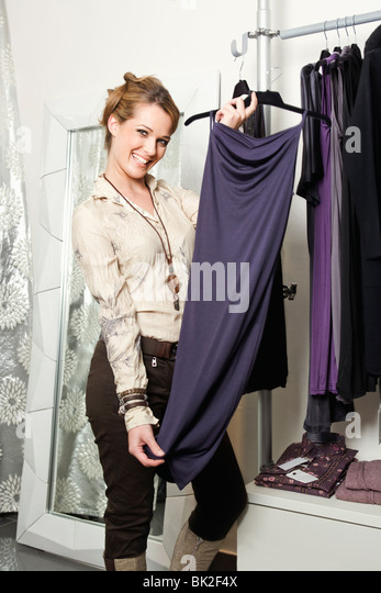 A woman holding up a new dress - Stock Image