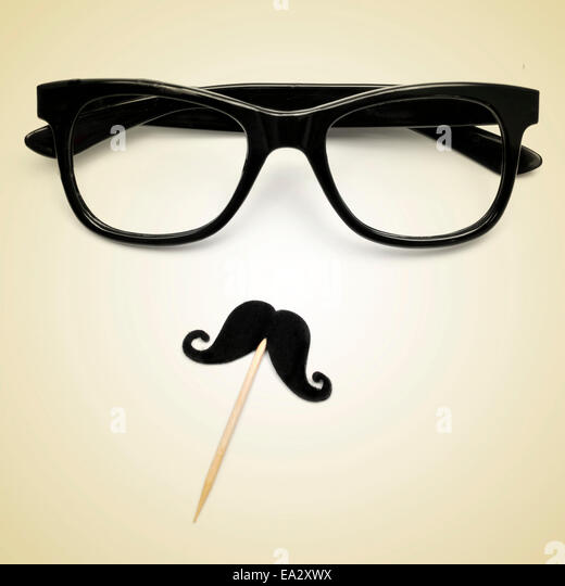 eyeglasses and a moustache depicting a gentleman or a hipster guy on a beige background, with a retro effect - Stock Image