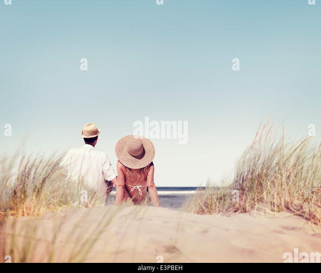 Couple Sitting and Looking at the View of the Beach - Stock Image