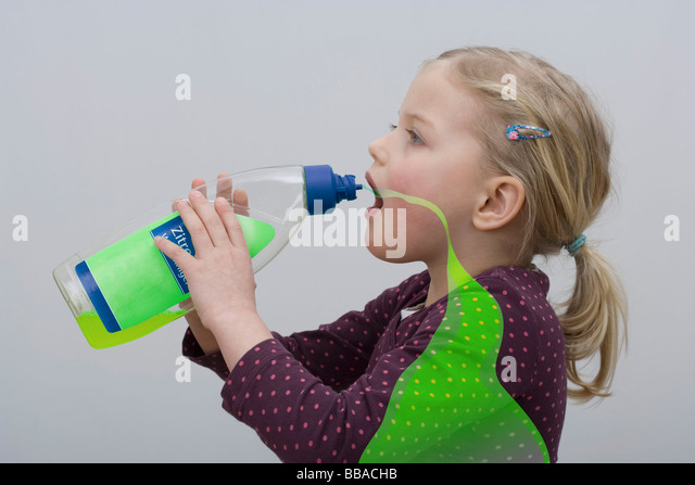 A young girl drinking from a bottle of cleaning fluid - Stock Image