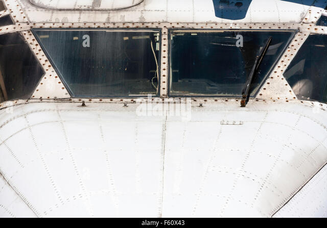 Silver bare metal of plane fuselage, looking straight at the cockpit. - Stock Image