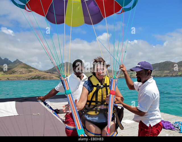 A middle aged woman age 50s preparing to go parascending ( parasailing ) in Mauritius - Stock Image