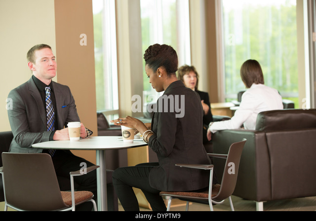 co workers having coffee in the break room - Stock Image