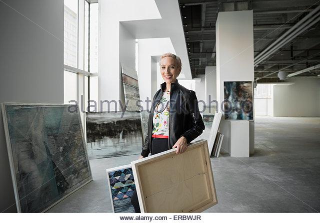 Portrait confident artist carrying paintings in art gallery - Stock-Bilder