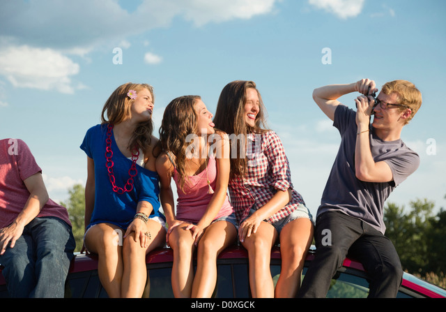 Friends sitting on car roof, young man taking photograph - Stock Image