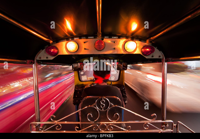 Tuk Tuk or auto rickshaw in motion at night, Bangkok, Thailand, Southeast Asia - Stock Image
