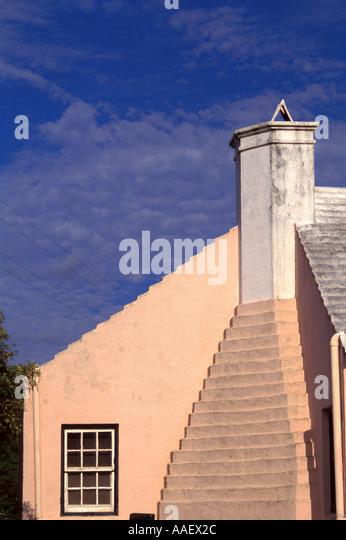 Bermuda Pink Building traditional bermudan architecture white roof chimney symbol  Blue Sky background atlantic - Stock Image