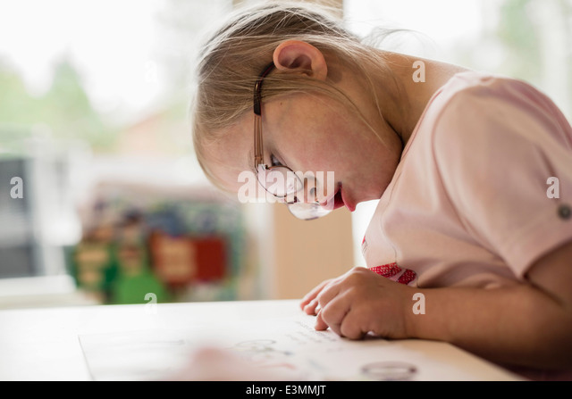Girl with down syndrome studying at table - Stock-Bilder