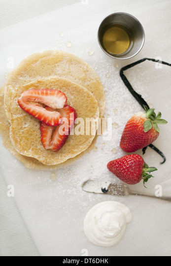 A selection of party desserts. Pancakes, freshly cooked, with strawberries and a drink. Organic food. - Stock Image