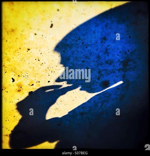Shadow of a young boy eating - Stock Image