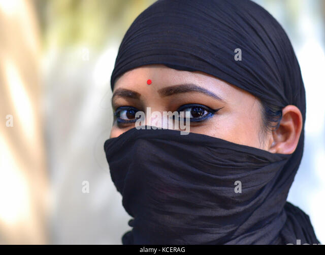 Three-quarter view of a young Assamese Hindu beauty with almond-shaped eyes, covering her hair and face with a secular, - Stock Image