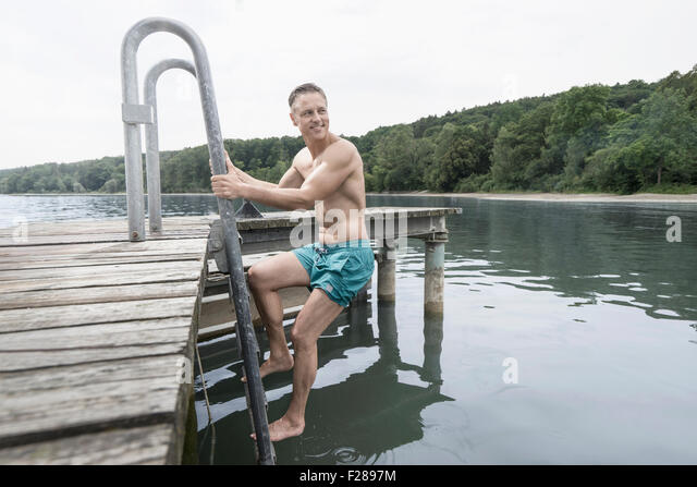 Mature man climbing ladder of lake, Baden-Wurttemberg, Bavaria, Germany - Stock-Bilder