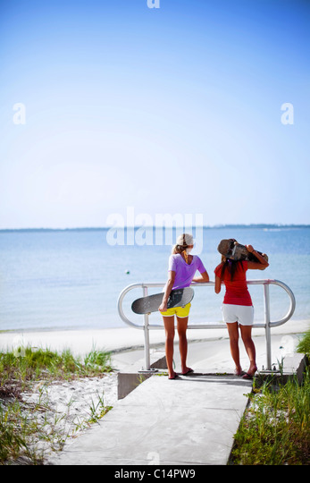 Two girls rest on a rail and look out over the Santa Rosa Sound near Pensacola Beach, Florida. - Stock Image