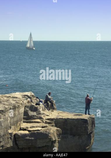 Fishermen fishing from rock and yacht Portland Bill Dorset England UK Europe - Stock Image