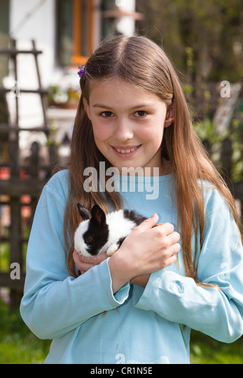 Girl, 10 years old, with pet rabbit - Stock Image