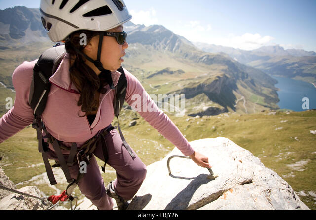 A young woman takes a moment to enjoy the scenery while engaging in the sport of Via Ferrata in the French Alps. - Stock-Bilder