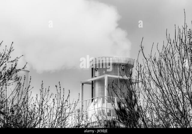 Black and white images of steam venting into darkened skies from a chimney at a china clay plant at Par beach, Cornwall. - Stock Image