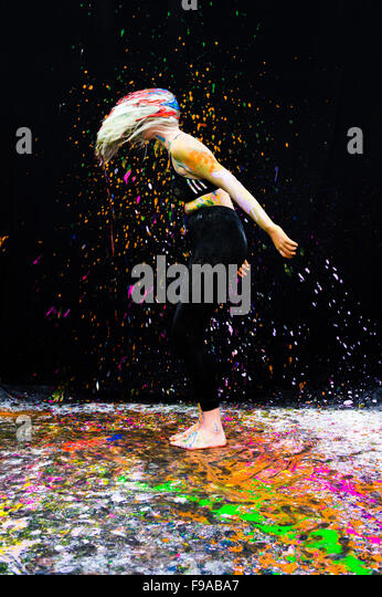 A young woman girl female  model standing against a black background splattered with splashes of multicoloured paint - Stock-Bilder
