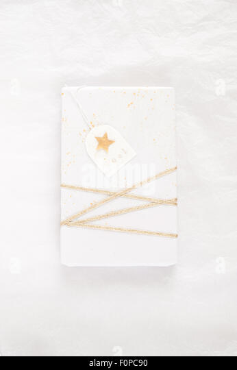 simple gift wrapping with white tissue paper splattered with random gold paint and decorated with gold ribbon and - Stock Image