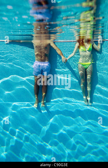 Young couple holding hands in swimming pool, underwater view - Stock-Bilder