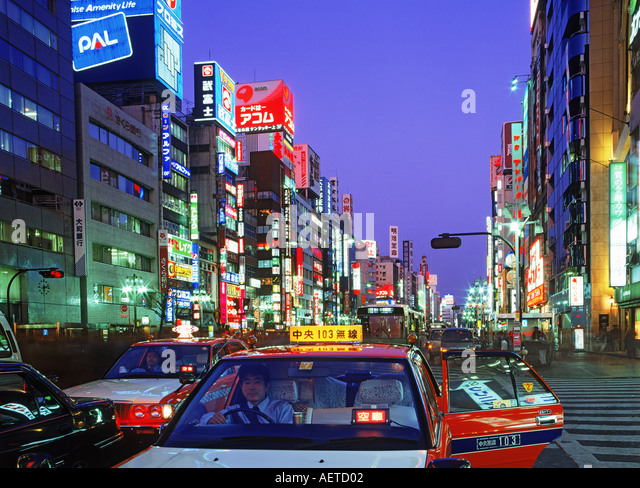 Taxis and foot traffic in Ginza district of Tokyo at night - Stock Image