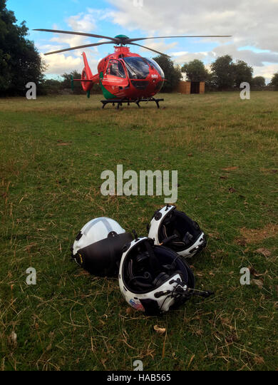 Wales Air Ambulance helicopter landed on top of riverbank to lift off casualty at The Warren Hay on Wye Powys Wales - Stock Image