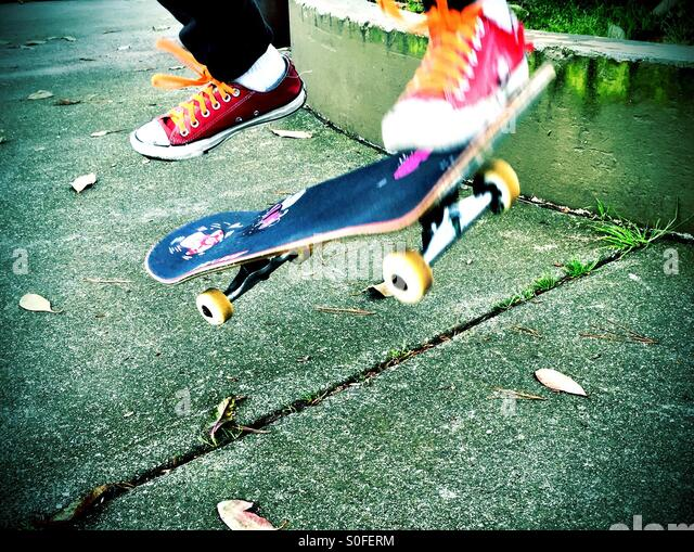 Getting air, kicking, jumping, flipping up skateboard while clad in red sneakers with orange shoelaces. - Stock-Bilder