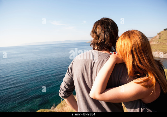 Young couple looking at horizon - Stock Image