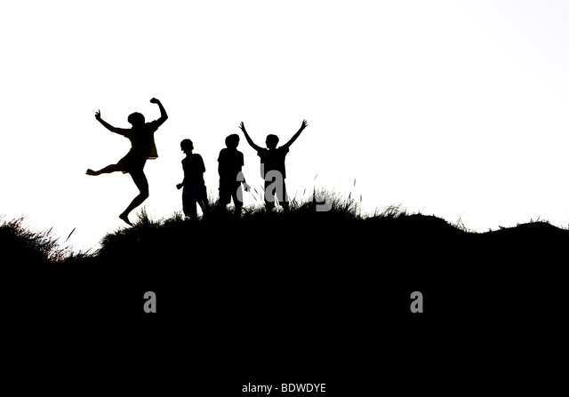 Four teenagers leaping into the air, silhouetted against a bright sky - Stock Image