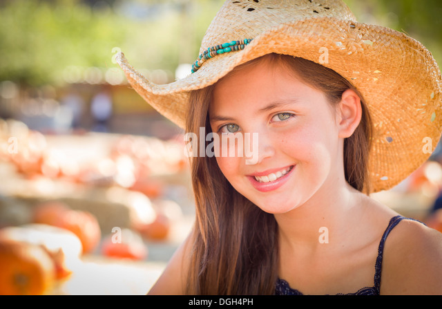 Preteen Girl Portrait Wearing Cowboy Hat at Pumpkin Patch in Rustic Setting. - Stock Image