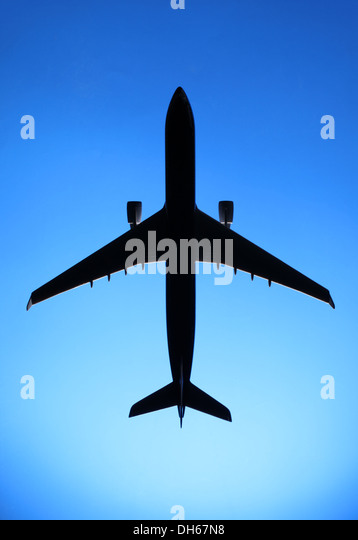 A plastic model of a commercial airplane airplane flying in blue sky - Stock Image