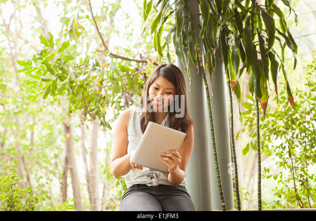 Young woman using digital tablet outdoors - Stock Image
