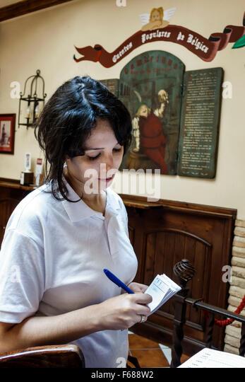 Spain Europe Spanish Hispanic Toledo Cerveceria Gambrinus bar restaurant business inside Hispanic woman waitress - Stock Image