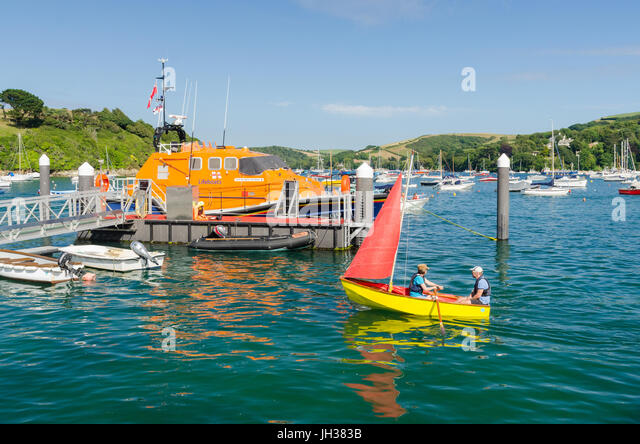 Brightly coloured sailing dinghy in the water in the Salcombe estuary - Stock Image