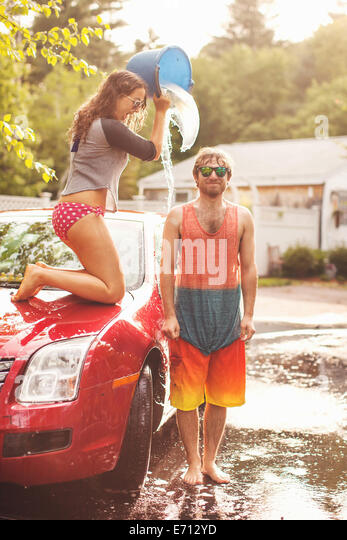 Young woman pouring bucket of water on man's head - Stock-Bilder