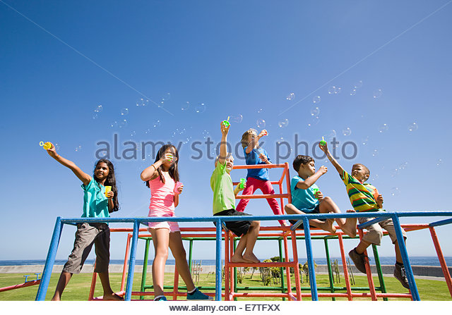 Children blowing bubbles on monkey bars at playground - Stock Image