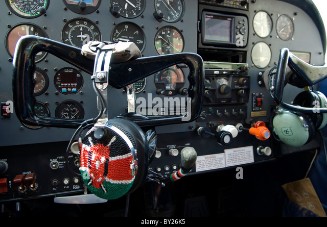Kenya;  The controls of a Cessna light aircraft.  The pilot's headset is covered in a beaded Kenyan flag. - Stock Image