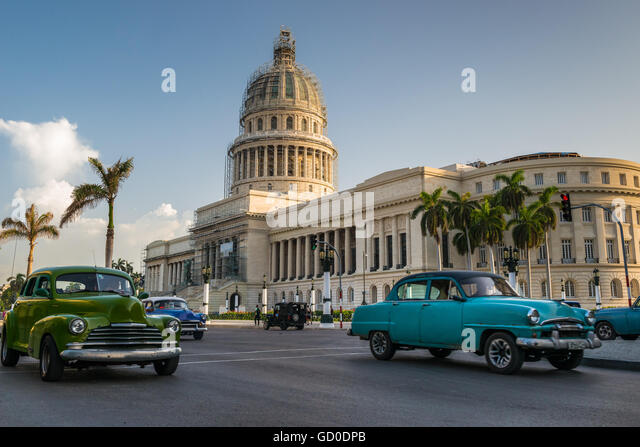 Old American cars drive past the Capitol building in Havana, Cuba. - Stock Image
