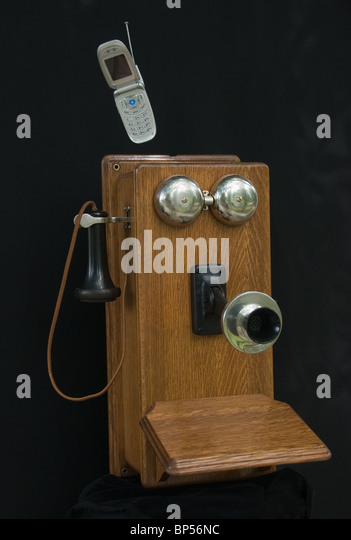 Old wooden wall telephone with cell phone displayed - Stock Image