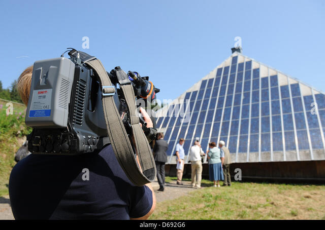 A cameraman films the solar panels on the roof of the inn Rappendecker Huette in Oberried, Germany, 27 July 2012. - Stock Image