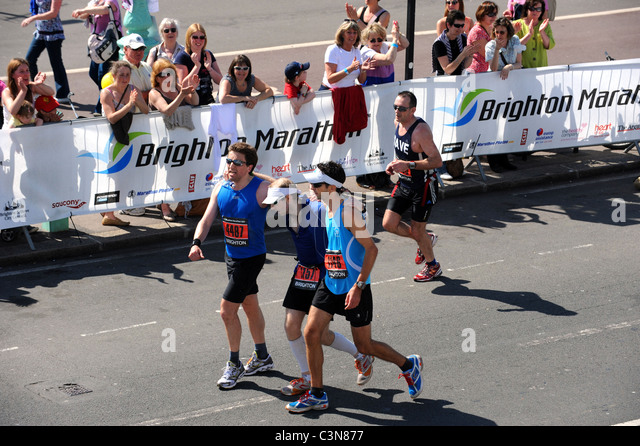 Brighton Marathon 2011 - Exhausted runners help each other to the finish line - Stock Image