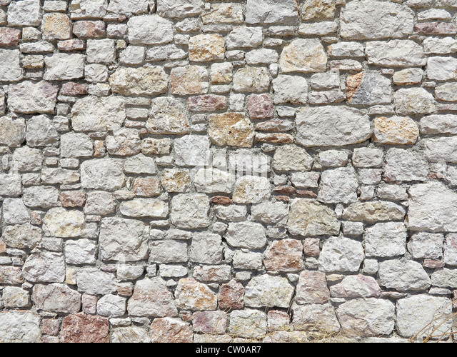 Block stone wall made from irregular sized stone blocks - Stock Image