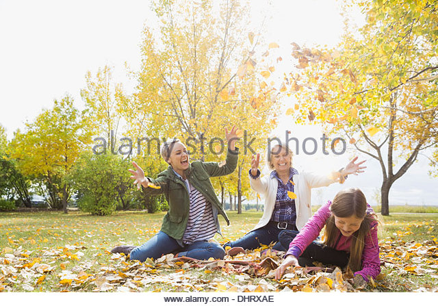 Three generation females playing with autumn leaves in park - Stock Image